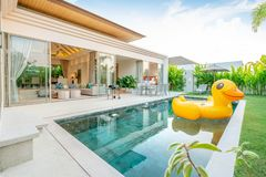 Home or house Exterior design showing tropical pool villa with greenery garden, sun bed, umbrella, pool towels and colorful. Home or house Exterior design royalty free stock images