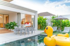 Home or house Exterior design showing tropical pool villa with greenery garden, sun bed, umbrella, pool towels and floating duck royalty free stock photo