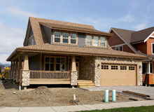 Home House Exterior. Exterior view of a new custom home under construction with brown roofing stock images