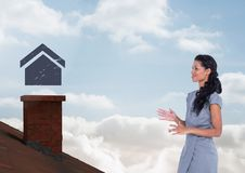 Home icon over roof chimney and Businesswoman standing on Roof with chimney and blue sky. Digital composite of Home icon over roof chimney and Businesswoman Stock Image