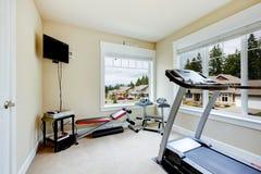 Home idrottshall med utrustning, vikter och TV:N. Arkivbild