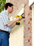 Home Improvement (1). Drilling Holes on the exterior of a brick house. Handy man wearing glasses is using a cordless drill royalty free stock photography