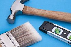 Home Improvement. Scene.  Hammer, Level and Paintbrush on Blue Stock Photos