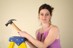 Home Improvement. Young woman standing on a step ladder holding a hammer Stock Image
