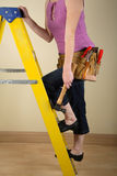 Home Improvement. Young woman standing on a step ladder wearing a toolbelt Royalty Free Stock Photo