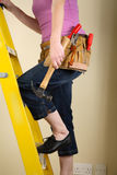 Home Improvement. Young woman standing on a step ladder wearing a toolbelt Royalty Free Stock Images