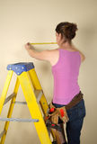 Home Improvement. Young woman standing on a step ladder using a tape measure Stock Photo
