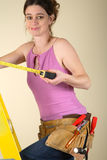 Home Improvement. Young woman standing on a step ladder using a tape measure Stock Photos