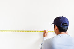 Home improvement. A shot of a man using measurement tape for home improvement royalty free stock image