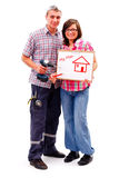 Home improvement. A happy young couple standing, showing their improvement plans Royalty Free Stock Images
