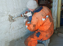 Home Improvement. Drilling holes in a brick house.  man using a  drill Royalty Free Stock Photos