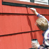 Home Improvement. Man painting house window trim with black paint Stock Image