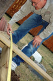 Home Improvement. Man measures deck for home improvement, do it yourself work Stock Photos