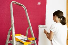 Home improvement. Beautiful woman painting wall with paint roller. Home renovation concept royalty free stock image
