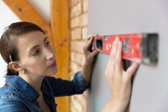 Home improvement. Beautiful women making a mark on wall with level. royalty free stock photos