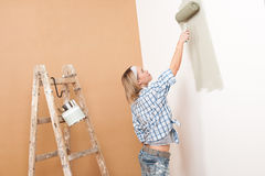 Home improvement: Blond woman painting wall. With paint roller Royalty Free Stock Image