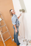 Home improvement: Blond woman painting wall Stock Images