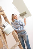 Home improvement: Blond woman painting wall. With paint roller Royalty Free Stock Photo