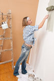 Home improvement: Blond woman painting wall Royalty Free Stock Photography