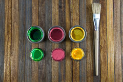 Home improvement, colorful paint cans on the clear wooden backgr Royalty Free Stock Images