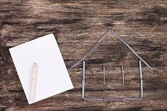 Home concept. Wooden model house on a work table with tools and empty spiral notebook. Home improvement concept - Wooden model house on a work table with tools royalty free stock image