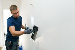Home improvement - construction worker  renovating apartment walls. Home improvement - construction worker with plastering tools renovating apartment walls Royalty Free Stock Photo