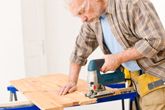 Home improvement - handyman cut wood with jigsaw. In workshop Stock Photos