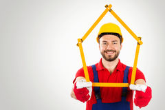 Home improvement - handyman with house shaped ruler in hands on royalty free stock photo