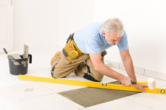 Home improvement - handyman laying ceramic tile. Home improvement, renovation - handyman laying ceramic tile with level stock photo
