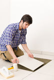 Home improvement - handyman laying tile. Home improvement, renovation - handyman laying tile, trowel with mortar royalty free stock images