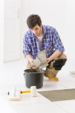 Home improvement - handyman laying tile. Home improvement, renovation - handyman laying tile, trowel with mortar stock images