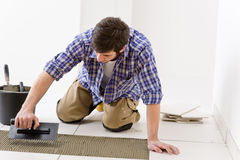 Home improvement - handyman laying tile Stock Image