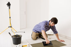 Home improvement - handyman laying tile. Home improvement, renovation - handyman laying tile, trowel with mortar stock photo