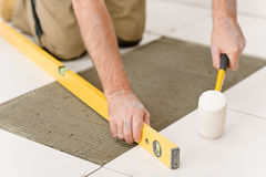 Home improvement - handyman laying tile. Home improvement, renovation - handyman laying tile with level stock images