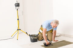Home improvement - handyman laying tile. Home improvement, renovation - handyman laying tile, trowel with mortar stock image