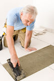 Home improvement - handyman laying tile. Home improvement, renovation - handyman laying tile, trowel with mortar stock photos