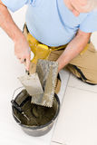 Home improvement - handyman laying tile. Home improvement, renovation - handyman laying tile, trowel with mortar royalty free stock photo