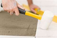 Home improvement - handyman laying tile. Home improvement, renovation - handyman laying tile with level royalty free stock image