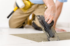 Home improvement - handyman laying tile. Home improvement, renovation - handyman laying tile, trowel with mortar royalty free stock photography