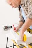Home improvement - handyman measure porous brick Royalty Free Stock Images