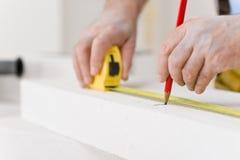 Home improvement - handyman measure porous brick. In workshop Stock Images