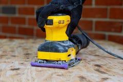 Home improvement handyman sanding wood in workshop Royalty Free Stock Photography