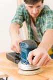 Home improvement - handyman sanding wooden floor. In workshop Royalty Free Stock Images