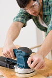 Home improvement - handyman sanding wooden floor Stock Photography