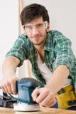 Home improvement - handyman sanding wooden floor. In workshop Royalty Free Stock Photography