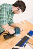 Home improvement - handyman sanding wooden floor. In workshop Royalty Free Stock Photo