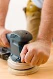 Home improvement - handyman sanding wooden floor. In workshop Stock Image