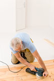 Home improvement - handyman sanding wooden floor Stock Images
