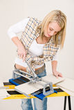 Home improvement - handywoman cutting tile Stock Images