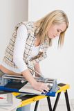 Home improvement - handywoman cutting tile. With jigsaw Stock Image